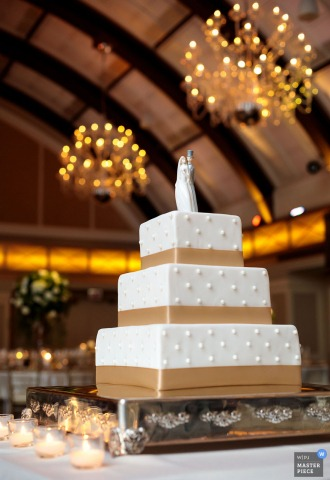 Chicago wedding photographer captured this beautiful image of a simple, square, white wedding cake wrapped in gold stripes while chandeliers glow in the background