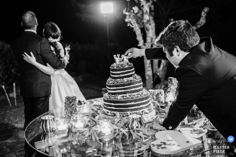 Libson wedding photographer created this black and white picture of the finishing touches being added to the cake while the happy couple pose for pictures