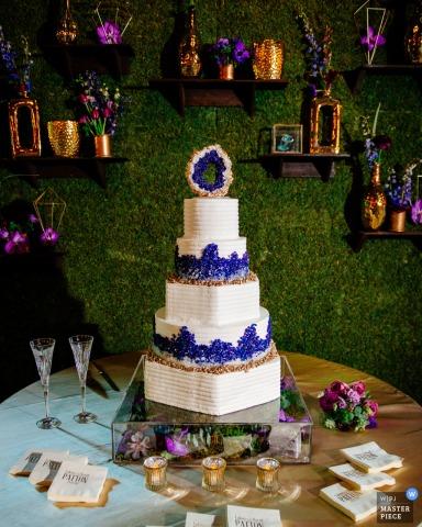 El fotógrafo de bodas de Birmingham capturó esta foto de un pastel blanco rematado con flores púrpuras bellamente exhibidas frente a una pared verde cubierta en muchos estantes y jarrones