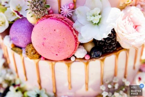 Der Hochzeitsfotograf von Noord Holland hat diese Nahaufnahme einer Hochzeitstorte mit Beeren, Blumen und Makronen aufgenommen