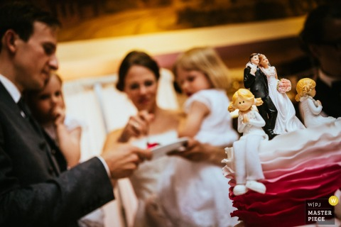 This photo of a bride and groom and their two daughters enjoying pink and white wedding cake while in the foreground, a close up shot of the cake adorned with a topper for all members of the family was taken by a wedding photographer