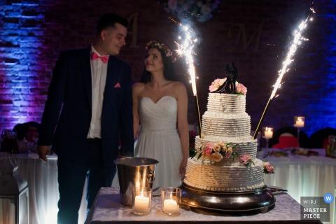 Der dokumentarische Hochzeitsfotograf aus Krakau, Malopolskie, machte dieses Bild von der Braut und dem Bräutigam, die neben ihrem Kuchen mit Wunderkerzen / Feuerwerkskörpern darauf standen.