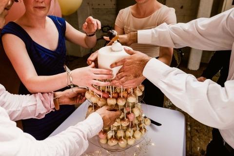 Fotografía de boda documental de manos construyendo un pastel por un fotógrafo de estilo de reportaje en el Reino Unido