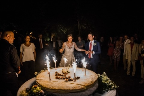 France Wedding Reportage Photographer Karol Robache captured the bride and groom with fireworks on their cake at night.