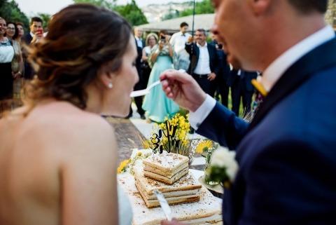 Novio que alimenta a la novia un bocado de pastel por el fotógrafo de bodas Marinelli Fotografie en Italia