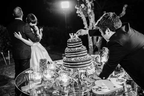 Wedding Photographer Pedro Vilela of Portugal crafted this black and white image during the reception of a vendor fixing the cake topper.
