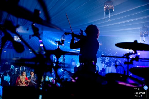 Gujarat wedding photographer captured the silhouette of a fiddler against a background of blue and purple stage lights