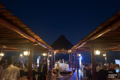 Phoenix wedding photographer captured this night time photo of the bride and groom at the sweetheart table under a gazebo