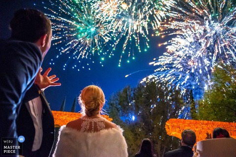 San Diego wedding photographer captured this image of a bride and groom standing in awe under a royal blue sky lit up with fireworks