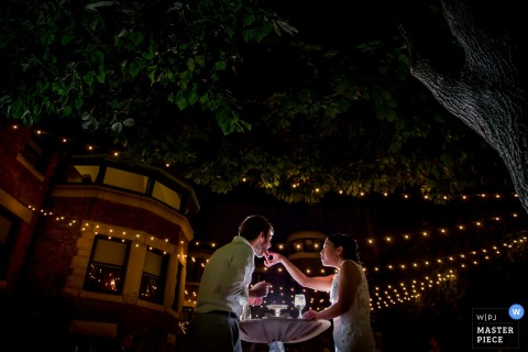 This photo of a bride and groom tenderly feeding each other cake under strings of twinkle lights on a tree lined street was captured by a Chicago wedding photographer