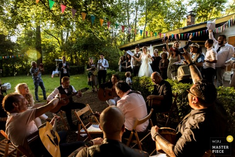 The casual atmosphere of this outdoor wedding reception being enjoyed by guests playing outside in a wooded clearing was captured by a Rotterdam wedding photographer