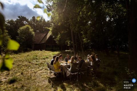 Le photographe de mariage de Rotterdam a créé cette image d'une réception de mariage intime au milieu d'une forêt ensoleillée, tandis qu'une cabine se dresse au loin.