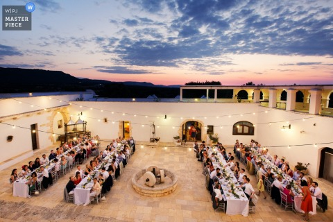 Lecce wedding photographer created this aerial image of a wedding reception being held in a brightly lit stone courtyard while the sun sets in the distance