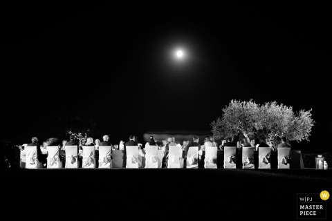 This black and white photo showing a long banquet table surrounded by wedding guests under a full moon, was captured from a distance by a Portofino wedding photographer