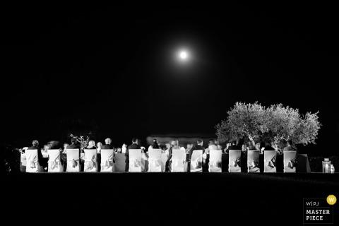 Dieses Schwarzweißfoto mit einem langen Banketttisch, der von Hochzeitsgästen bei Vollmond umgeben ist, wurde von einem Portofino-Hochzeitsfotografen aus der Ferne aufgenommen