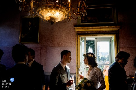 Turin wedding photographer captured this image of a bride and groom talking under a golden chandelier at their wedding reception