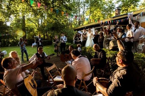 Les jeunes mariés riant et chantant lors de leur réception de mariage en plein air. Photo de mariage par Isabelle Hattink, Pays-Bas
