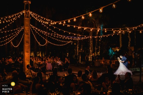 Cabo San Lucas wedding photographer captured this long distance photo of the bride and groom having their first dance outside under a spot light