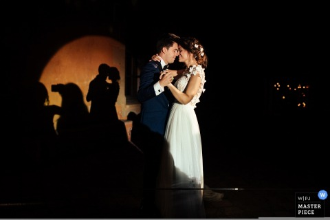 Madrid wedding photographer captures this tender first dance as the bride and groom dance slowly in the spotlight
