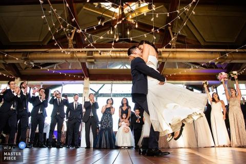New-Jersey Hochzeitsfotograf stellte dieses Bild eines Bräutigams her, der ihre Braut anhebt, um sie unter baumelnden Funkelnlichtern und herausgestellten hölzernen Lichtstrahlen zu küssen