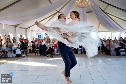 San Diego wedding photographer captured this bride and groom mid twirl as they have their first dance under a chandelier adorned reception tent