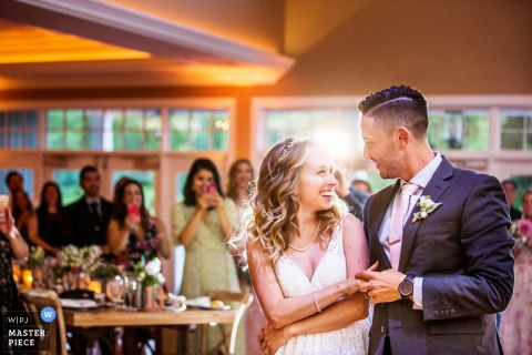 New Jersey wedding photographer captured this photo of the bride and grooms first dance while the sun shines through the window behind them