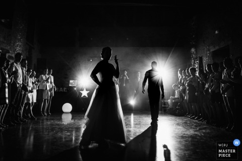 Pays de la Loire wedding photographer captured this black and white photo of a groom approaching the bride on the dance floor to being their first dance