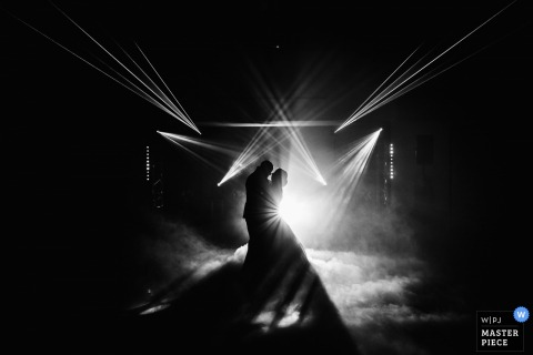 France wedding photographer captured the silhouettes of the bride and groom having their first dance amid spot lights and fog