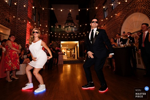 Baltimore wedding photographer captured this photo of the bride and groom doing a silly dance together in light up sneakers and matching sunglasses