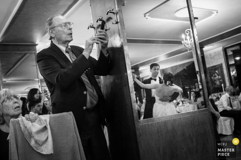 Calabria wedding photographer captured this photo of a man using his photo to record the first dance, that we can see reflected in a mirror next to him