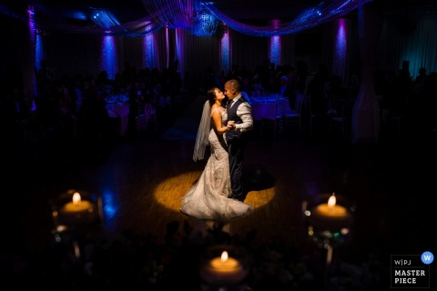 This photo of the bride and groom standing under a spotlight for their first dance while candles burn in the foreground and purple lights shine behind them was captured by a San Diego wedding photographer