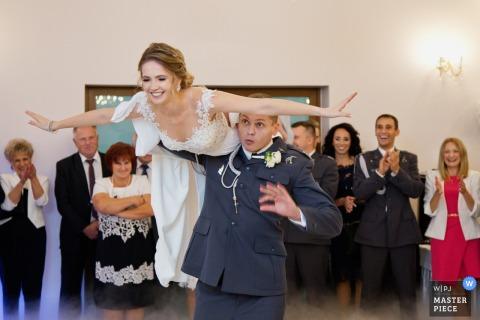 Krakau Malopolskie Hochzeitsfotograf erstellt dieses Bild eines eingetragenen Bräutigams fliegt seine neue Braut auf die Schulter, während die Gäste an der Rezeption jubeln.