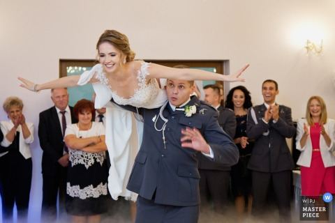 Krakow Malopolskie wedding photographer created this image of an enlisted groom flying his new bride on his shoulder while guests cheer at the reception.