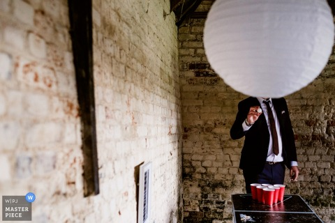 Deze humoristische foto van bruidegomsmannen die bier pong spelen terwijl een grote lantaarn zijn gezicht verduisterde werd gevangen door een het huwelijksfotograaf van Kent