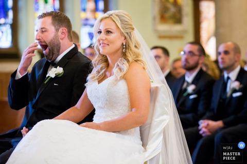 Esta foto de una radiante novia sonriendo pacientemente mientras el novio bosteza a su lado fue capturada por un fotógrafo de bodas de Nueva Jersey