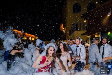 Sevilla-Hochzeitsfotograf nahm dieses Bild der Hochzeitsgäste gefangen, die im Schaum beim heraus feiern in der Straße während des Hochzeitsempfangs bedeckt wurden