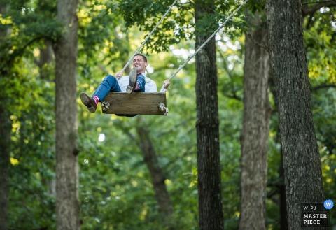 Fotograf ślubny Charlotte uchwycił ten figlarny wizerunek pana młodego na drewnianej huśtawce w środku słonecznego lasu