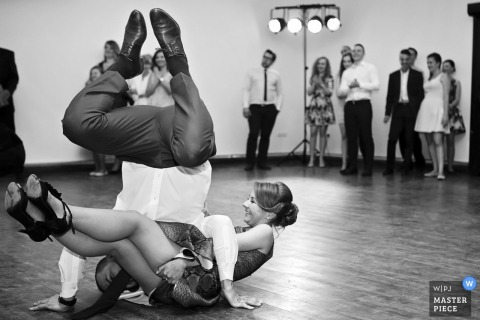 Der Hochzeitsfotograf von Mielec hat dieses lustige Foto von zwei Hochzeitsgästen aufgenommen, die sich während des Hochzeitsempfangs auf der Tanzfläche verhedderten