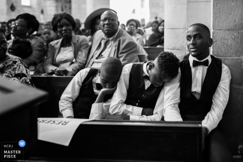 Seine-et-Marne wedding photographer captured this black and white image of two young groomsmen asleep on anothers shoulder during the church ceremony