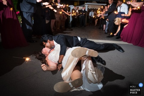 Detroit wedding photographer captured this silly photo of a bride and groom falling to the dance floor while holding a sparkler as wedding guests cheer them on