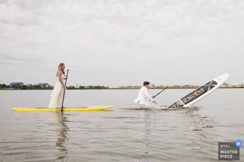 Fotograf ślubny z Baltimore uchwycił ten humorystyczny wizerunek wiosła dla panny młodej i pana młodego w ubraniach ślubnych, gdy pan młody wpada do wody