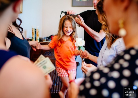 Birmingham wedding photographer captured this photo of a little girl excitedly getting her hair curled before the wedding begins