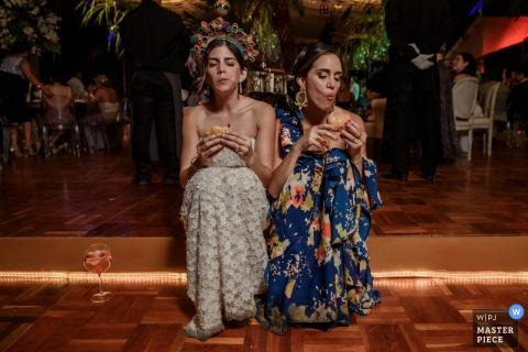 De huwelijksfotograaf van Madrid ving deze foto van de bruidzitting op de vloer naast haar moeder genietend van een sandwich