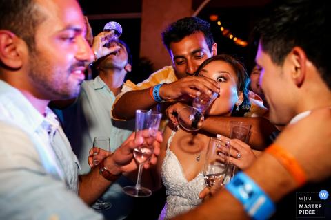 Het huwelijksfotograaf van Playa del Carmen ving dit beeld van een verraste bruid die hulp met haar drank op de dansvloer krijgt