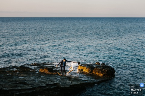 Portofino wedding photographer captured this humorous photo of a bride falling into the ocean while the groom grabs her by the dress