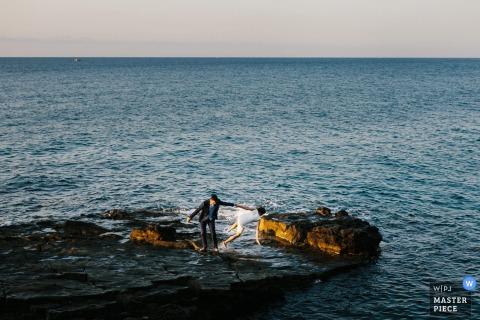 Portofino Hochzeitsfotograf nahm dieses humorvolle Foto einer Braut, die in den Ozean fällt, während der Bräutigam sie durch das Kleid ergreift