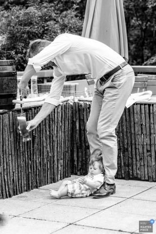 La photographe de mariage de Munich a capturé cette photo en noir et blanc humoristique d'un invité au mariage qui pose son bébé par terre alors qu'il remplit son verre dans un distributeur