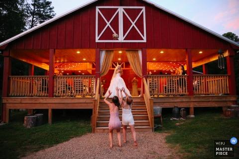 Fotograf ślubny Knoxville uchwycił to zdjęcie dwóch drużek domagających się bukietu, gdy panna młoda zrzuca go z najwyższego stopnia domu pomalowanego na biało i czerwono, by wyglądać jak stodoła