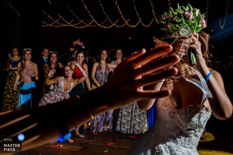 Lima wedding photographer captured the wedding guests waiting patiently for the bride to throw her bouquet under strings of twinkling lights
