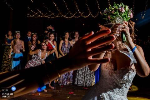 Fotograf ślubny w Limie chwycił gości weselnych, cierpliwie czekając, aż panna młoda rzuci swój bukiet pod sznurki migoczących świateł